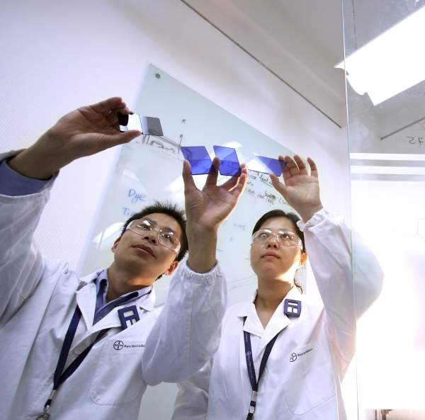 The polycarbonate colour laboratory in the integrated Bayer site in the Shanghai Chemical Industry Park. Two employees evaluate colour chips produced from Makrolon. Image courtesy of Bayer MaterialScience AG.